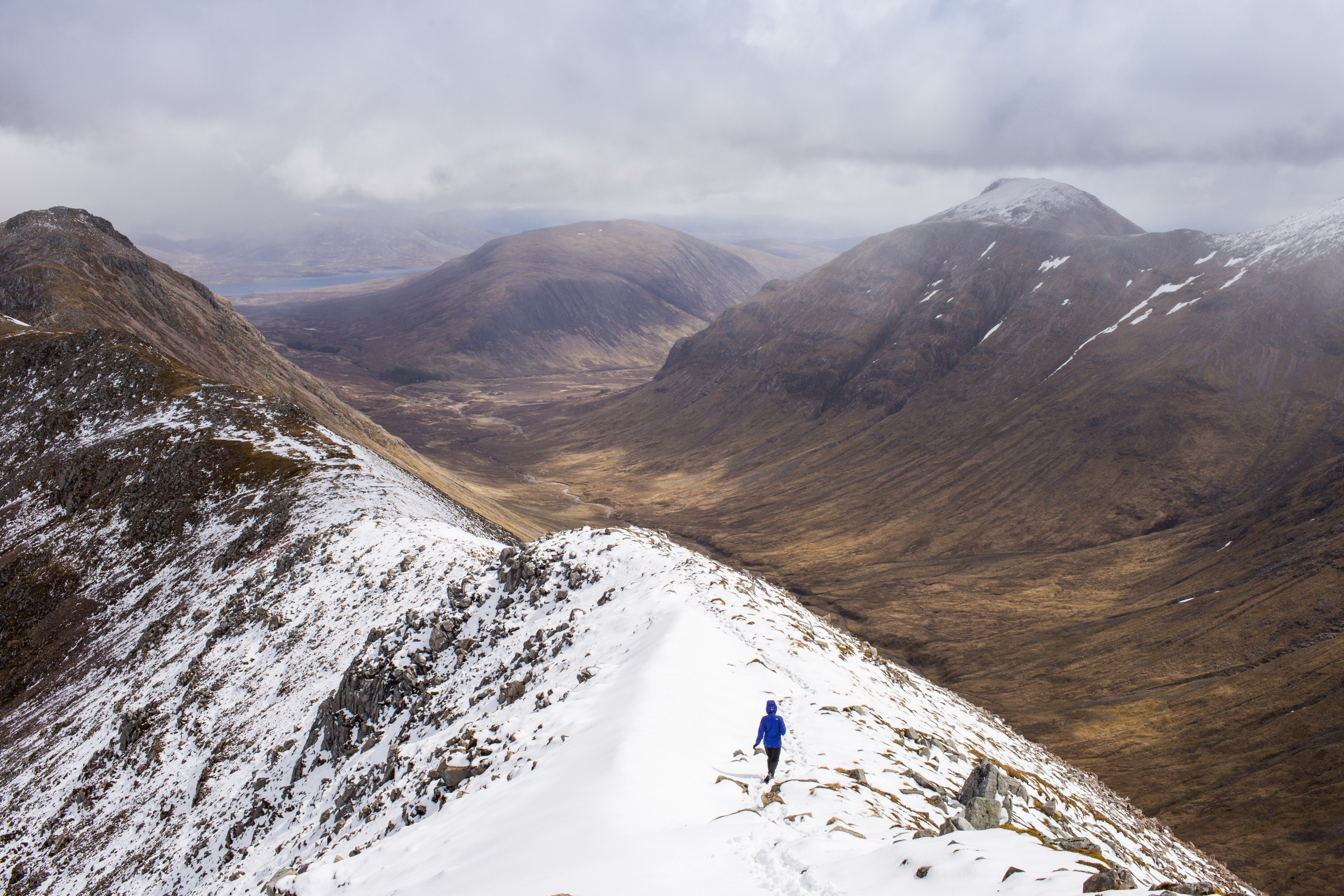 A person walking on a light dusting of snow in Glencoe Scotland