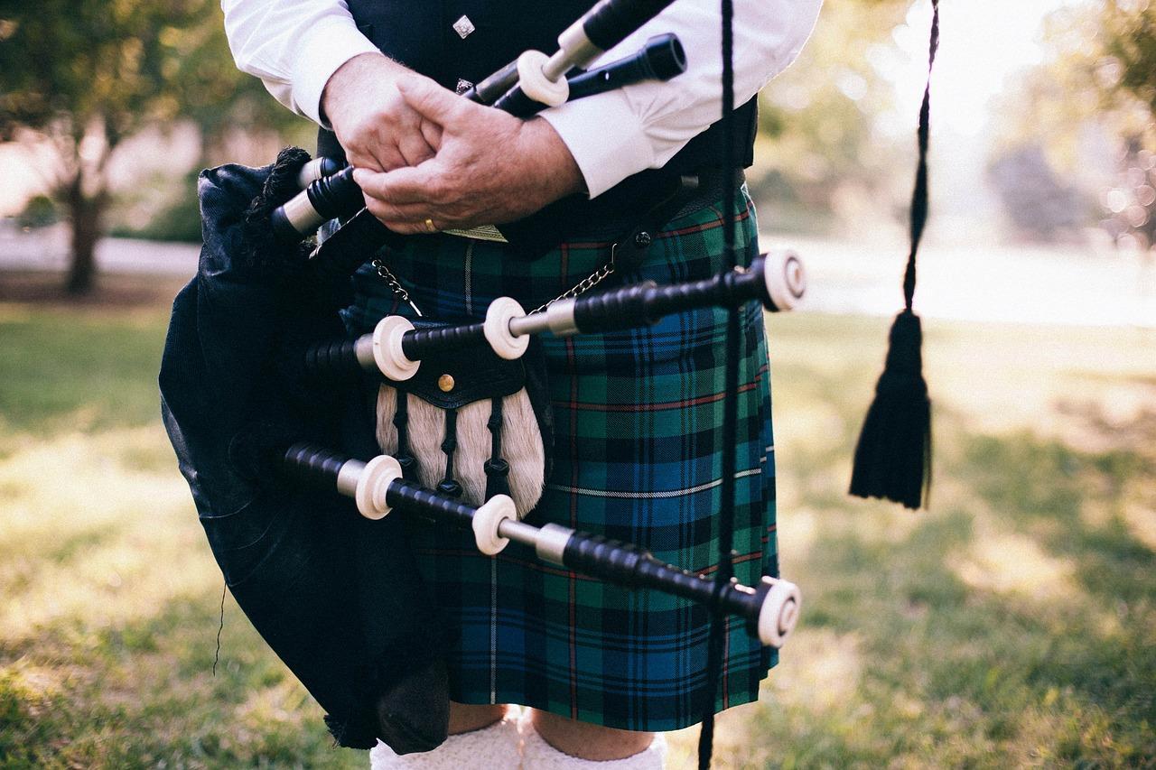 A piper wearing a kilt in a Mackenzie tartan