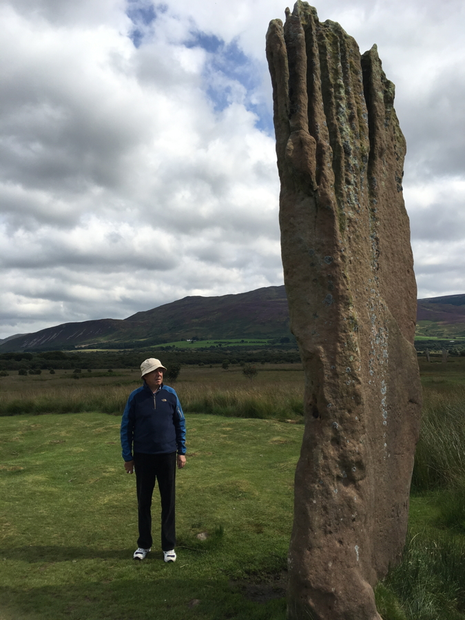 A person beside a towering standing stone on a trip to Scotland